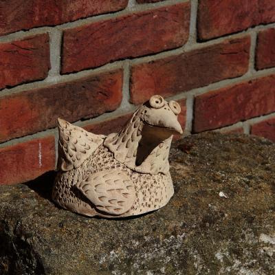 keramický pták nohatý ležící